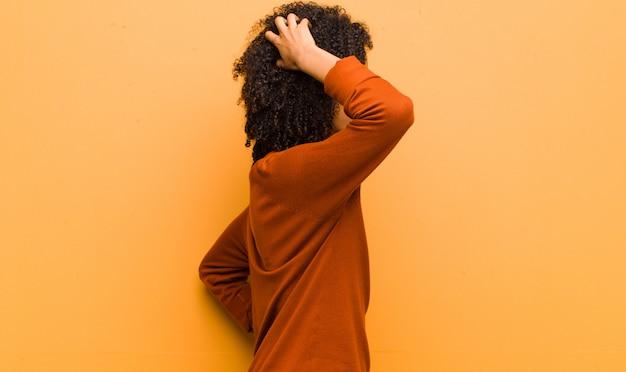 Sentirse desorientado y confundido, pensar en una solución, con la mano en la cadera y otra en la cabeza, vista trasera