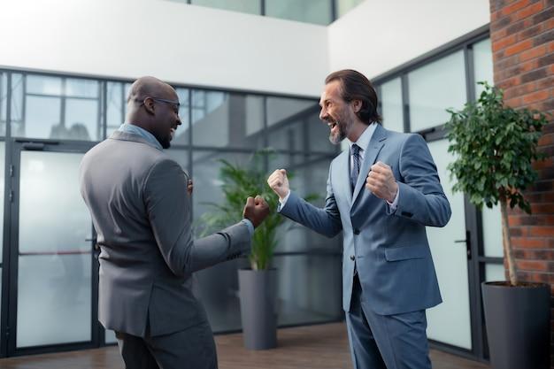 Sentirse extremadamente feliz. dos prósperos empresarios que se sienten extremadamente felices después de una reunión exitosa