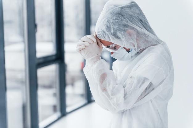 Sentirse mal, cansado y deprimido. retrato de doctora científico en bata de laboratorio, gafas defensivas y máscara