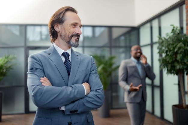 Sentirse motivado. hombre de negocios canoso barbudo que se siente motivado antes de la negociación con socios