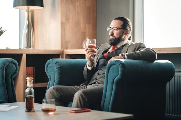 Sentirse preocupado. defensor experimentado que bebe un poco de whisky y fuma un cigarro mientras se siente preocupado
