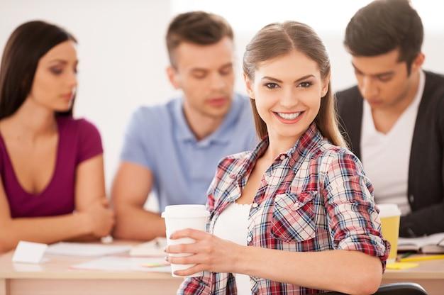 Sentirse seguro de su examen final. cuatro estudiantes alegres sentados juntos en el escritorio y estudiando mientras hermosa mujer mirando por encima del hombro y sonriendo