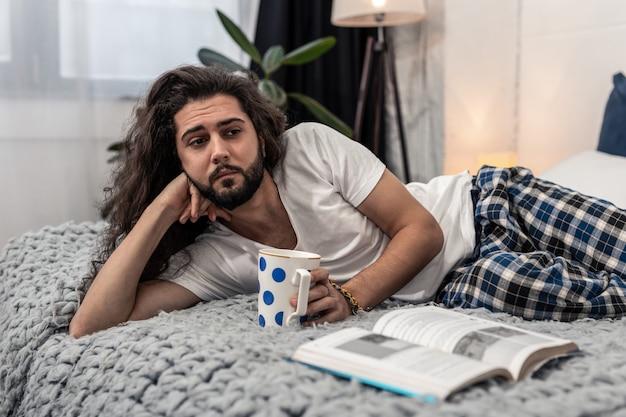 Sentirse solo. hombre pensativo triste bebiendo té mientras está solo en casa