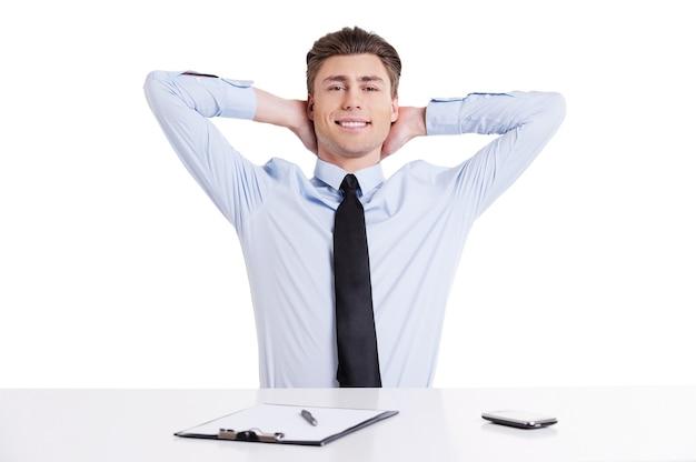 Sentirse tranquilo y seguro. apuesto joven en camisa y corbata sentado en la mesa y tomados de la mano detrás de la cabeza mientras aislados en blanco