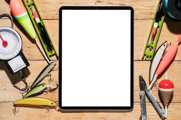 Señuelo de pesca; flotador de pesca alicate y balanza cerca de la tableta digital con pantalla blanca en el escritorio