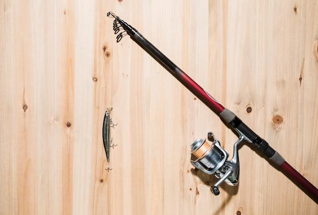 Señuelos de pesca en la caña de pescar sobre la superficie de madera