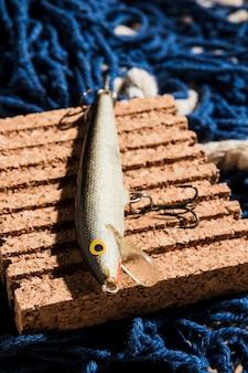 Señuelos de pesca en el panel de corcho sobre la red de pesca