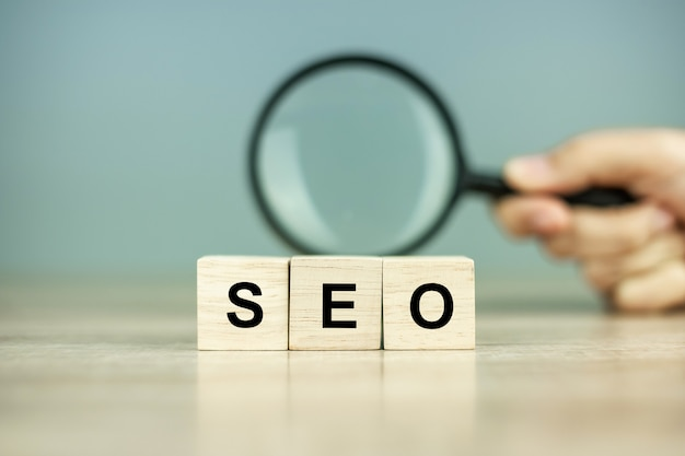 Seo (search engine optimization) cubos de texto de texto y lupa en la mesa de madera. concepto de idea, visión, estrategia, análisis, palabra clave y contenido