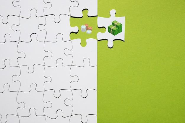 Separación de moneda y billete de banco en rompecabezas sobre fondo verde