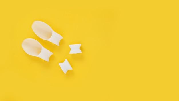 Separador de dedos de silicona blanca sobre fondo amarillo. prevención y tratamiento del hallux valgus