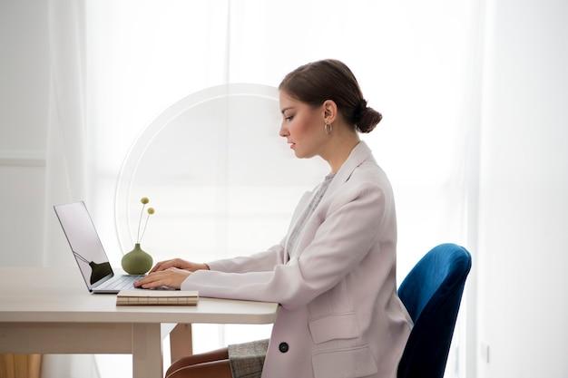 Separador de mesa con mujer trabajando en una computadora portátil Foto gratis