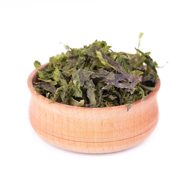 Seque las algas wakame en el tazón de fuente de madera, aislado en blanco. col rizada, comida seca asiática.