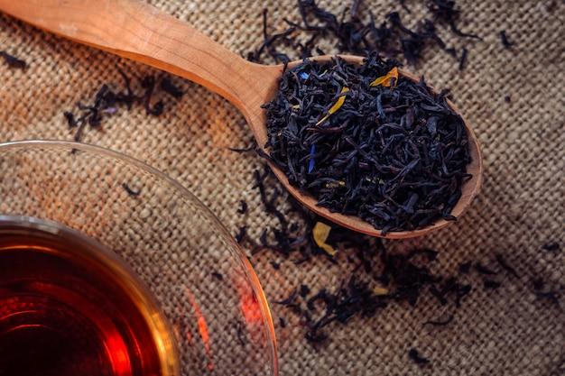 Seque las hojas de té con aditivos y té preparado en una taza de vidrio sobre un fondo oscuro de arpillera