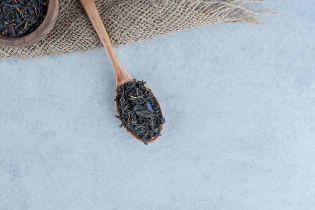 Seque las hojas de té en el cuenco de madera y con una cuchara sobre una toalla sobre mármol.