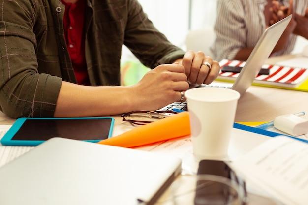 Ser atento. cerca del estudiante que mantiene las manos en la computadora portátil y escucha a sus compañeros de grupo