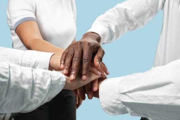 Ser un buen equipo. trabajo en equipo y comunicaciones. manos masculinas y femeninas sosteniendo aisladas sobre fondo azul de estudio. concepto de ayuda, asociación, amistad, relación, negocios, unión.