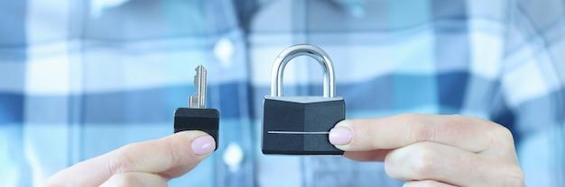 El ser humano tiene llave y candado en su mano seguro de propiedad contra concepto de subvenciones Foto Premium