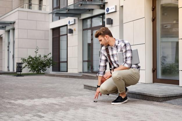 Ser incómodo. buen hombre guapo dejando caer sus llaves mientras tiene prisa