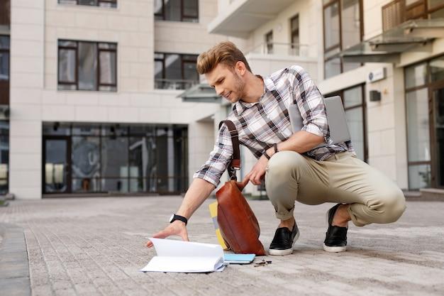 Ser incómodo. buen hombre guapo tomando un libro del suelo después de dejarlo caer