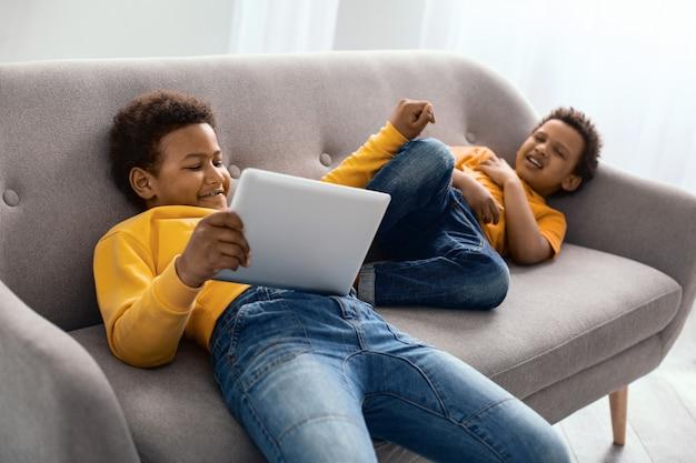 Ser un malvado. niño preadolescente de pelo rizado sentado en el sofá y jugando un juego en la tableta mientras aleja a su hermano pequeño interrumpiendo su juego
