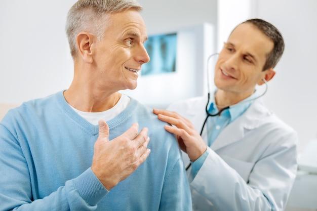 Ser optimista. hombre positivo encantado alegre sonriendo y volviéndose hacia su médico mientras se siente optimista