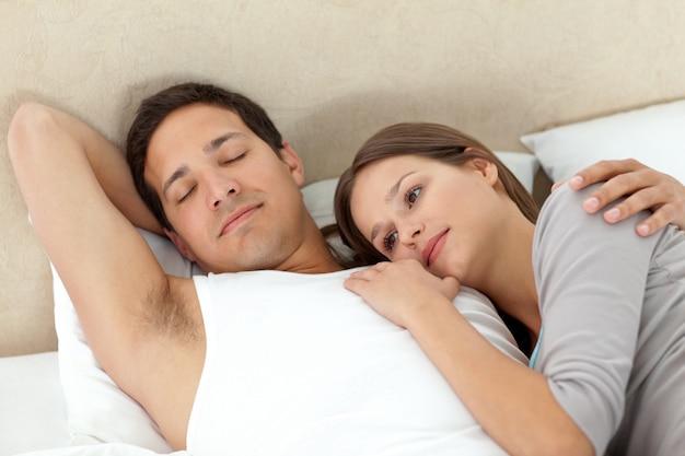 Serena mujer acostada sobre los brazos de su novio mientras duerme