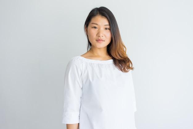 Seria hermosa joven mujer china en blusa blanca mirando a cámara.