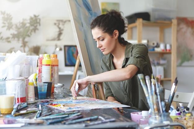 Seria morena joven y bella mujer sentada en un estudio de arte, tomando pinturas de colores del tubo mientras crea una gran obra maestra en el caballete, se preocupa por su trabajo y tiene una buena imaginación