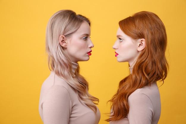 Serias dos damas con brillantes labios de maquillaje