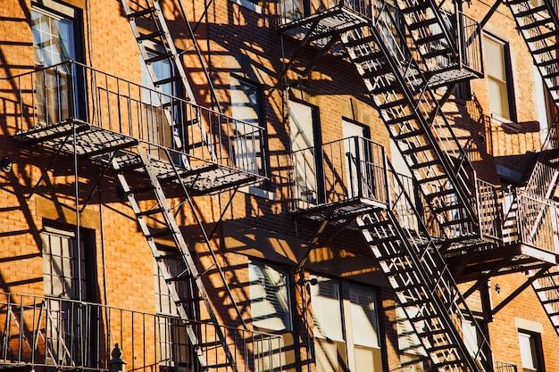 Serie de escaleras de escape en caso de incendio en la fachada de un edificio de apartamentos de ladrillo en la ciudad