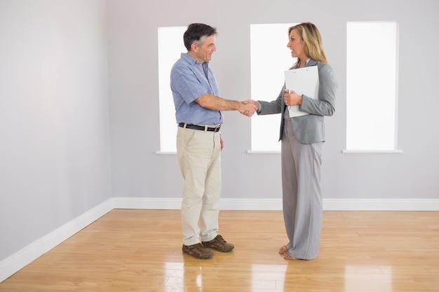 Serio agente de bienes raíces agitando la mano de su comprador