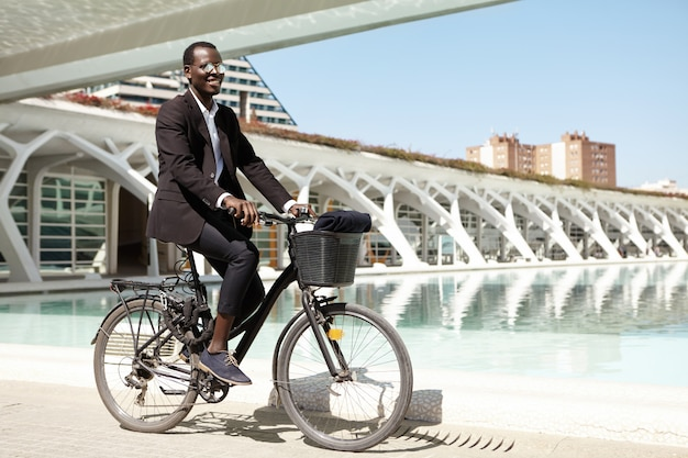 Serio empresario europeo de piel oscura con elegante traje negro y gafas de sol de espejo, de pie al aire libre con su bicicleta mientras espera almorzar con su pareja, enviándole mensajes en el teléfono inteligente