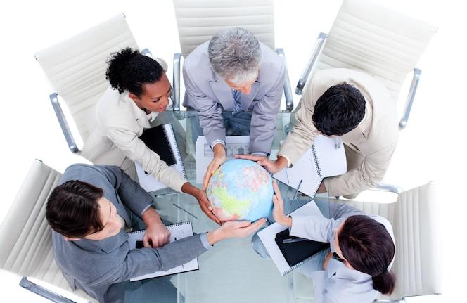 Serio equipo de negocios internacionales sosteniendo un globo terrestre
