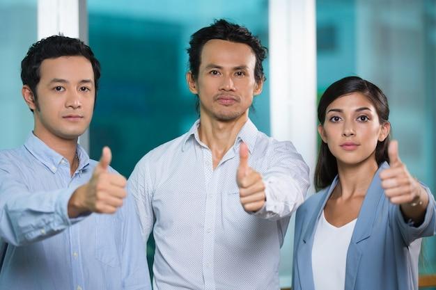 Serio equipo exitoso de negocios mostrando thumbs-up