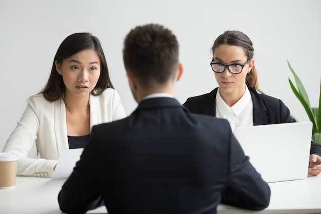 Serios no convencidos diversos gerentes de recursos humanos entrevistando a un candidato de trabajo masculino