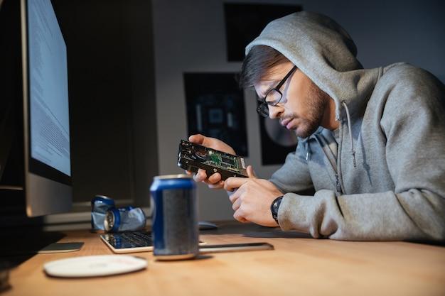 Seroso joven pensativo con gafas pensando y mirando en el disco duro roto en casa
