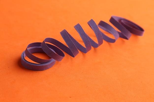 Serpentina de fiesta púrpura aislado sobre un fondo naranja