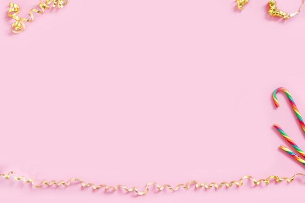 Serpentinas doradas y bastones de caramelo sobre fondo rosa pastel