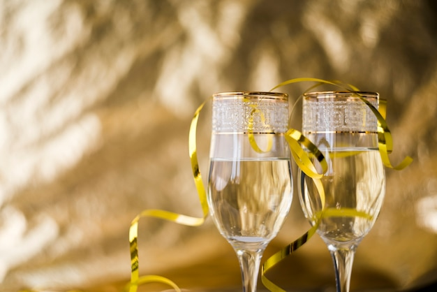 Serpentinas doradas sobre copas de champán transparentes contra un fondo borroso