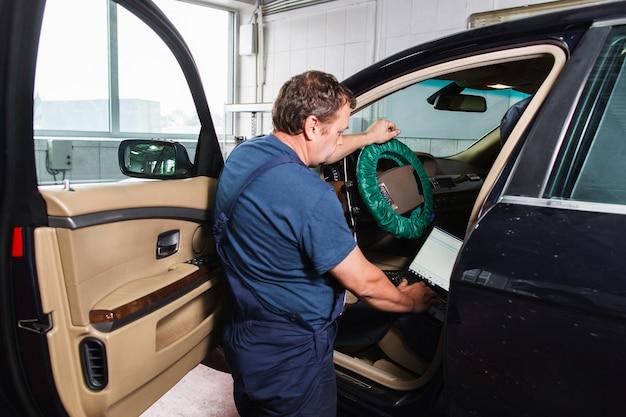 Serviceman haciendo diagnósticos de automóviles con laptop