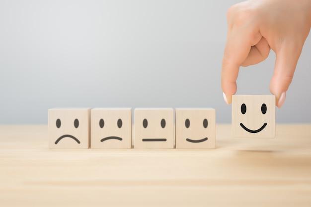 Servicio al cliente la mejor experiencia de calificación empresarial excelente. concepto de encuesta de satisfacción. la mano del empresario elige un cubo de madera sonrisa sobre fondo gris. copia espacio