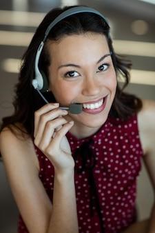 Servicio al cliente sonriente hablando por auriculares en la oficina