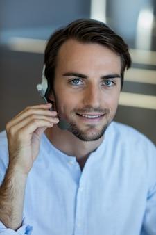 Servicio de atención al cliente sonriente tomando auriculares en la oficina