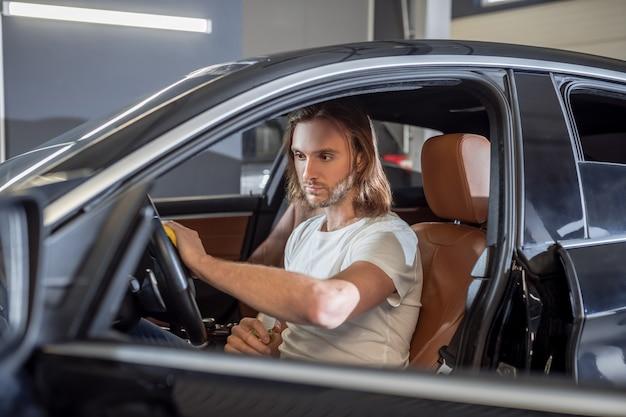 Servicio de auto. grave joven barbudo en camiseta ligera sentado en el salón del automóvil limpiando el volante con una servilleta y spray