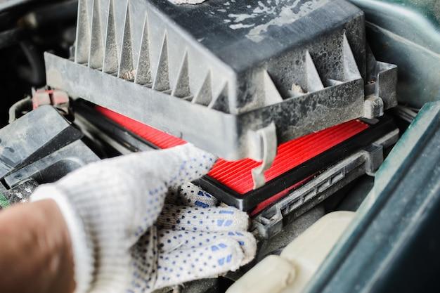 Servicio de auto. el mecánico reemplaza el filtro de aire.