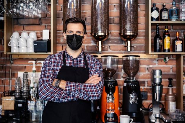 Servicio de bebidas durante la pandemia del virus corona. el hombre se para en el mostrador del restaurante y viste una camisa a cuadros y un delantal. una camarera tiene los brazos cruzados y lleva una máscara protectora