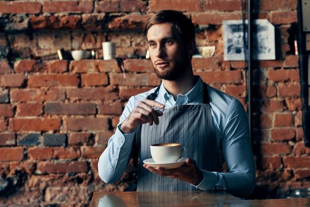 Servicio de camarero masculino una taza de café ordenando profesional