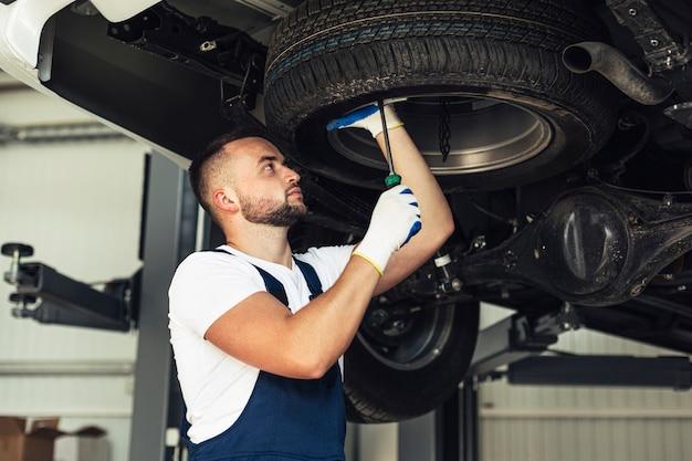 Servicio coche empleado masculino comprobando las ruedas del coche