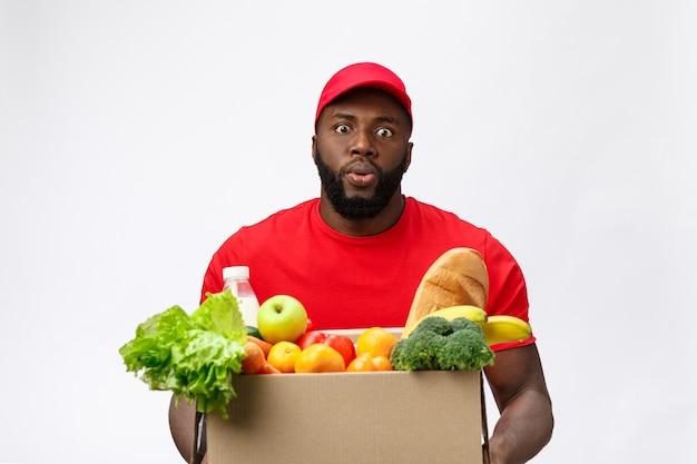 Servicio de entrega: apuesto hombre de entrega afroamericano que lleva la caja del paquete de comida y bebida de la tienda.