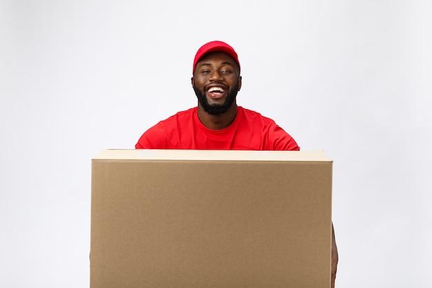 Servicio de entrega: apuesto hombre de entrega afroamericano que lleva la caja del paquete.